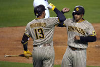San Diego Padres' Trent Grisham, right, celebrates his solo home run with Manny Machado (13) during the sixth inning of the team's baseball game against the Los Angeles Dodgers on Thursday, April 22, 2021, in Los Angeles. (AP Photo/Marcio Jose Sanchez)
