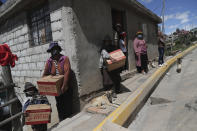 People wearing face masks hold food boxes distributed by the government during a lockdown to contain the spread of COVID-19 in a poor area on the outskirts of Quito, Ecuador, Wednesday, May 27, 2020. (AP Photo/Dolores Ochoa)