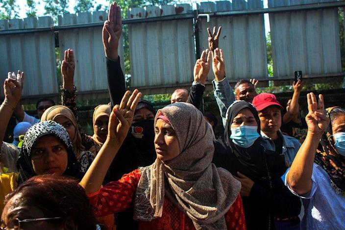 People flash three-finger salutes as they attend the funeral of U Khin Maung Latt in Yangon, 7 March