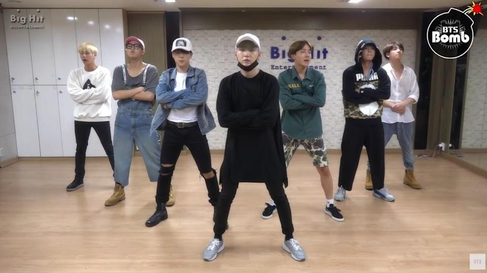 Bts stand in formation with their arms crossed in their former dance studio