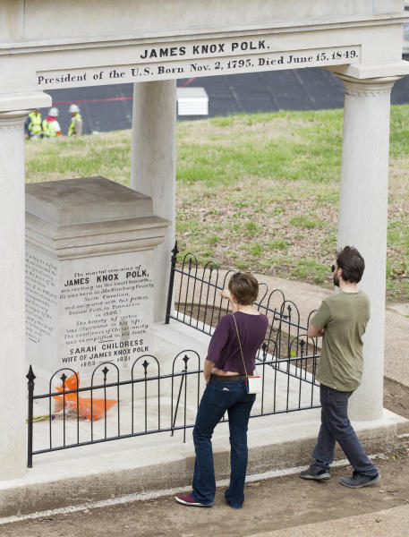 Visitors look at the burial place of President James K. Polk and his wife, Sarah Polk, on the grounds of the state Capitol in Nashville, Tenn., on Friday, March 24, 2017. A resolution being considered in the state Legislature calls for exhuming their bodies and moving them to the James K. Polk Home and Museum in Columbia, Tenn. (AP Photo/Erik Schelzig)