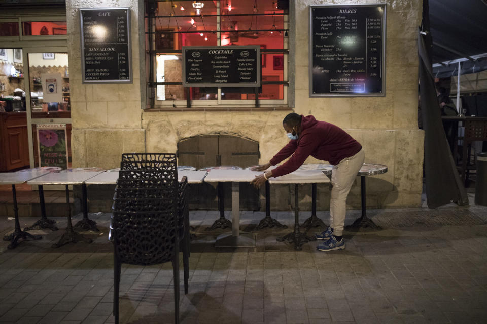 A waiter closes a bar terrace in Marseille, southern France, late Sunday Sept. 27, 2020. As restaurants and bars in Marseille prepared Sunday to shut down for a week as part of scattered new French coronavirus restrictions, Health Minister Olivier Veran insisted that the country plans no fresh lockdowns. (AP Photo/Daniel Cole)