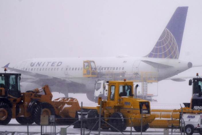 A United Airlines jetliner is sprayed with de-icing fluid while passing by a line of snow removal equipment on the way to a runway as a winter storm sweeps over the intermountain West Tuesday, Jan. 26, 2021, at Denver International Airport in Denver. Forecasters predict that the fast-moving storm could leave up to a foot of snow in some parts of the region before giving way to a front packing warmer temperatures for the rest of the week. (AP Photo/David Zalubowski)