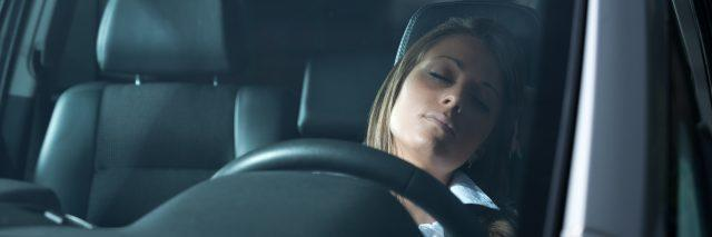 A picture of a woman sleeping in her car.