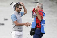 Andrew Landry, left, celebrates with his caddie Terry Walker after winning The American Express golf tournament on the Stadium Course at PGA West in La Quinta, Calif., Sunday, Jan. 19, 2020. (AP Photo/Alex Gallardo)