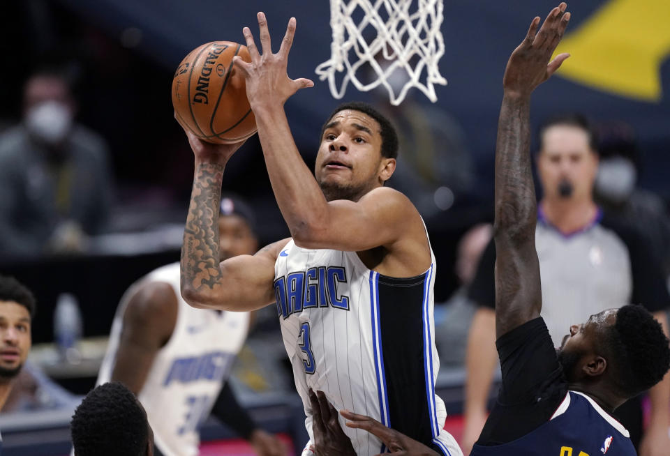 Orlando Magic forward Chuma Okeke drives to the basket and draws a foul from Denver Nuggets forward JaMychal Green during the first half of an NBA basketball game Sunday, April 4, 2021, in Denver. (AP Photo/David Zalubowski)