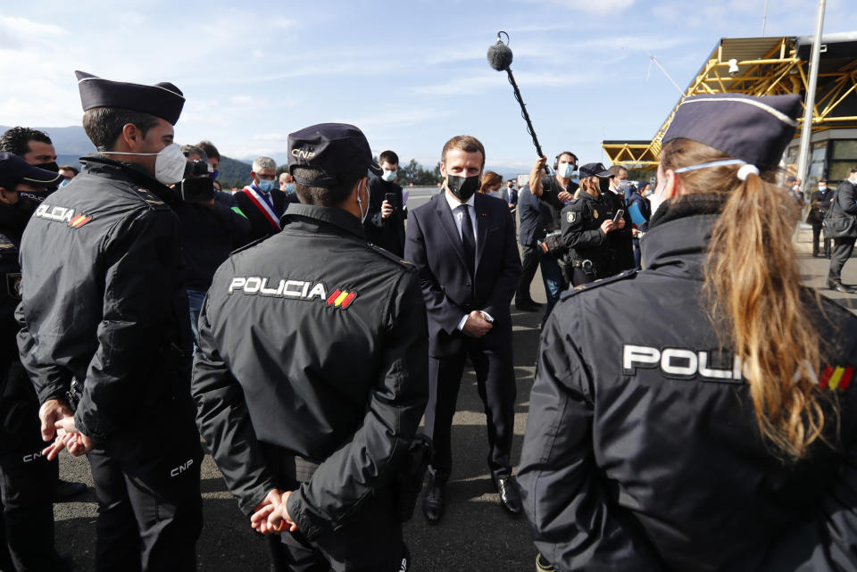 French President Emmanuel Macron greets Spanish police officers during a visit on the strengthening border controls at the crossing between Spain and France, at Le Perthus, France, Thursday, Nov. 5, 2020. (Guillaume Horcajuelo, Pool via AP)