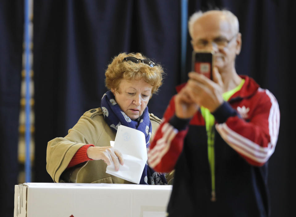 A man takes photos as a woman casts her vote in Bucharest, Romania, Sunday, Nov. 10, 2019. Voting got underway in Romania's presidential election after a lackluster campaign overshadowed by a political crisis which saw a minority government installed just a few days ago. (AP Photo/Vadim Ghirda)