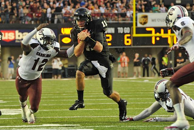 NASHVILLE, TN - AUGUST 30: Quarterback Jordan Rodgers #11 of the Vanderbilt Commodores tries to avoid Brison Williams #12 of the South Carolina Gamecocks at Vanderbilt Stadium on August 30, 2012 in Nashville, Tennessee. (Photo by Frederick Breedon/Getty Images)
