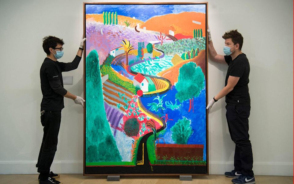 Art handlers with 'Nichols Canyon', a landscape by artist David Hockney, during an auction preview at Phillips in London - PA