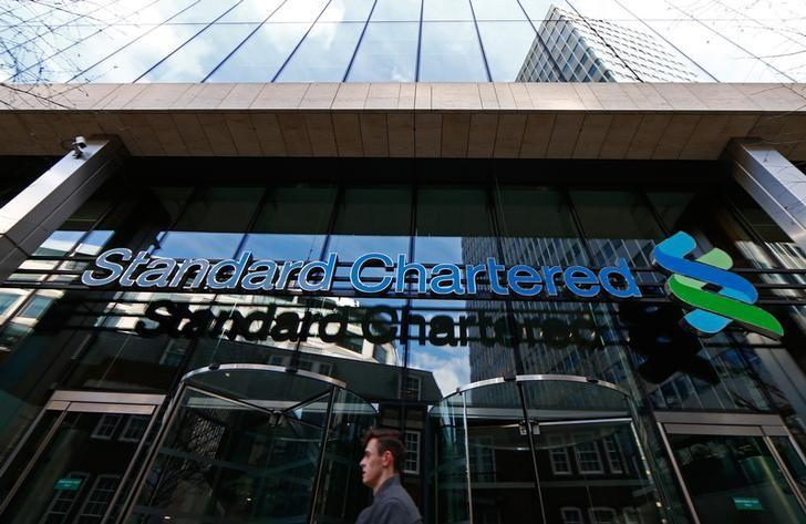 A man walks past the head office of Standard Chartered bank in the City of London