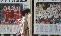 A man wearing face masks to protect against the spread of the coronavirus walks past extra papers reporting the start of the Tokyo Olympics in Tokyo Saturday, July 24, 2021. (AP Photo/Koji Sasahara)