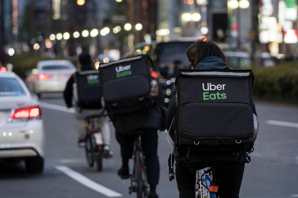 TOKYO, JAPAN - APRIL 11: Uber Eats delivery men ride bicycles through the Kabukicho entertainment area on April 11, 2020 in Tokyo, Japan. Tokyo Governor Yuriko Koike has requested that businesses including schools, athletic facilities, bars and restaurants to temporarily close or operate under reduced hours. The action follows a state of emergency that covers 7 of Japans 47 prefectures as the Covid-19 coronavirus outbreak continues to spread throughout the country. (Photo by Tomohiro Ohsumi/Getty Images)