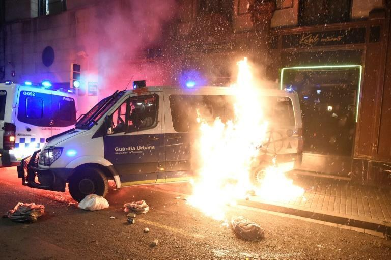 A Catalan police van is hit with a Molotov cocktail during a Barcelona protest against the controversial jailing of a rapper