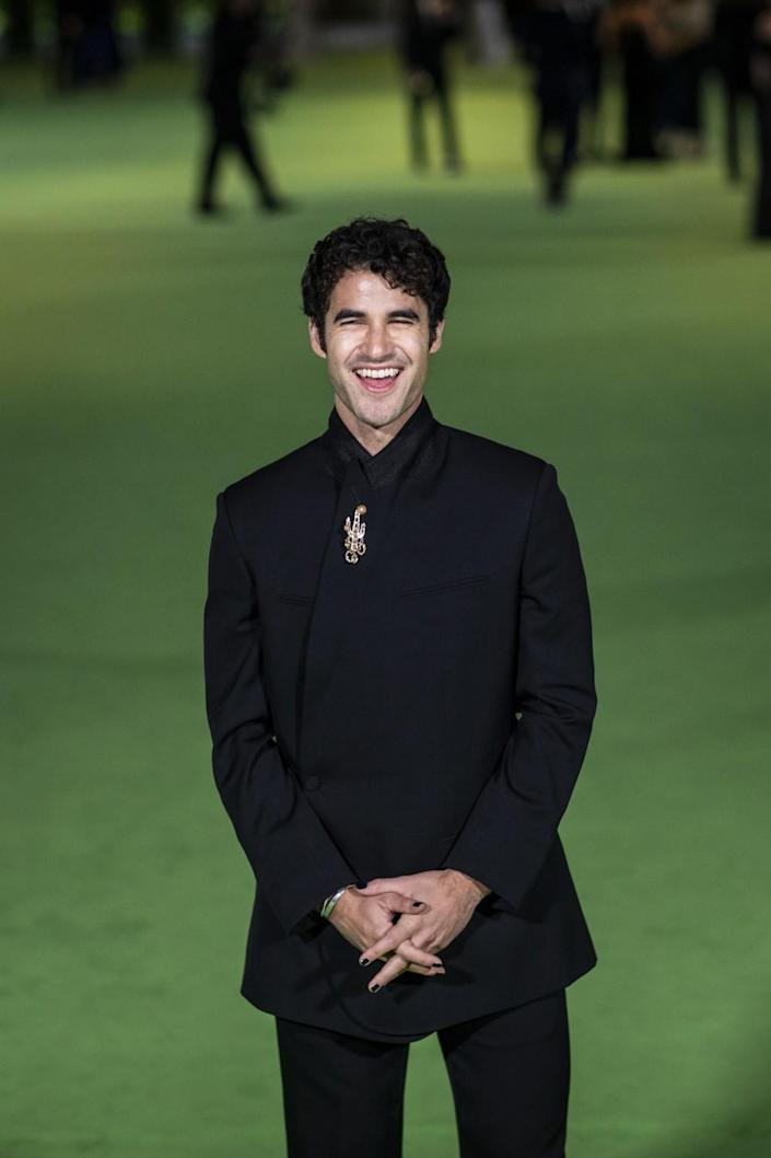 A man smiling in a black suit on a green carpet
