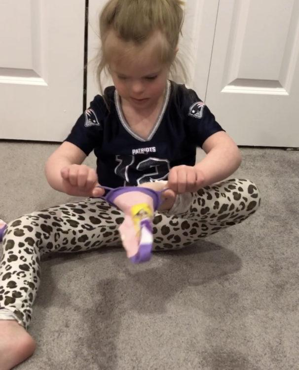 A little girl is sitting on the floor and playing with a toy.