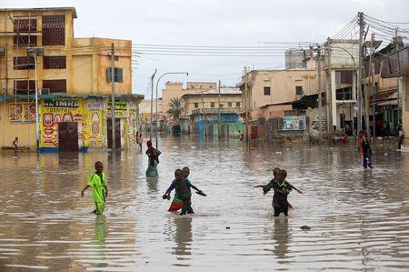 Children play in a flooded street in Hamerweyne district of Mogadishu, Somalia May 20, 2018. REUTERS/Feisal Omar/Files