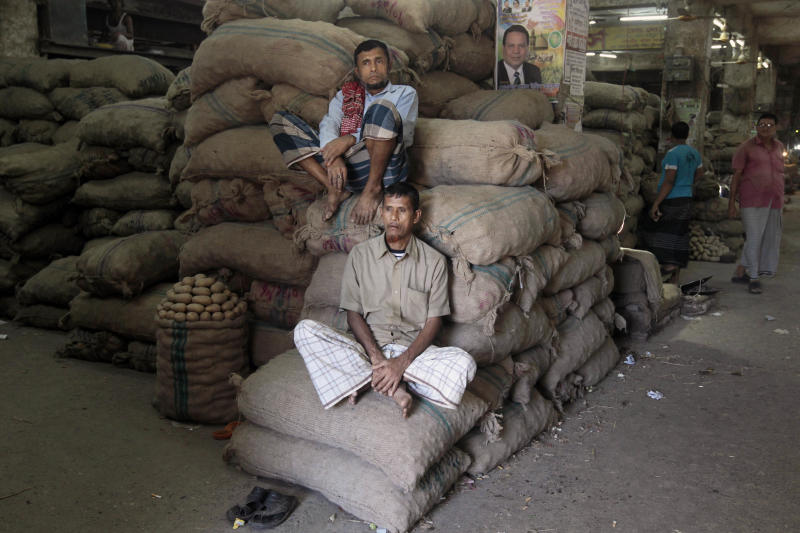 Bangladeshi shopkeepers sit on sacks at a wholesale market on the second day of a four-day general strike in Dhaka, Bangladesh, Monday, Nov. 11, 2013. Opposition enforced a four-day general strike to force Prime Minister Sheikh Hasina to quit and form a caretaker government made up of people from outside of mainstream political parties to oversee an election next year. (AP Photo/A.M. Ahad)
