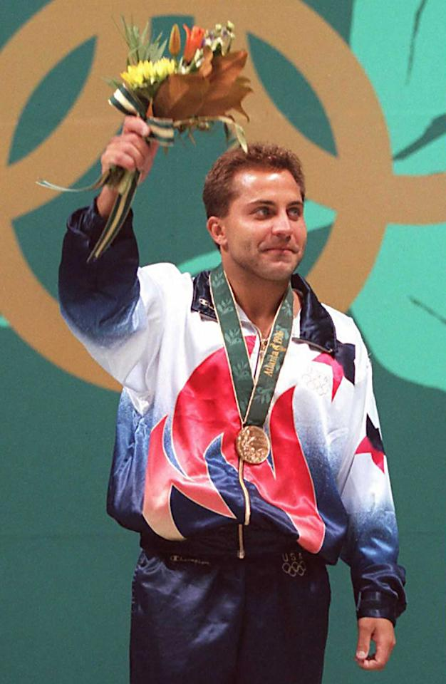 (FILES) This July 29 1996 file photo shows diver Mark Lenzi of the US displaying his gold medal after winning the bronze in the Olympic men's 3m springboard event in Atlanta, Georgia. Reports out of Greenville, North Carolina say that the 43-year-old Olympian died April 9, 2012. Lenzi was hospitalized twoo weeks ago after suffering from a series of fainting spells.    AFP PHOTO/ Tim CLARY/FILES (Photo credit should read TIMOTHY A. CLARY/AFP/Getty Images)