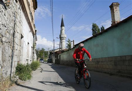 A cyclist rides a bicycle along a street in Bakhchisaray