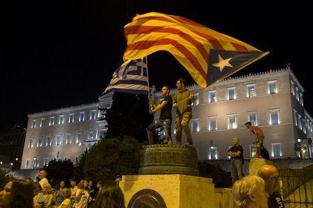 "Protesters wave a ""Estelada"" (Catalonian separatist flag) (R) and a Greek flag in front of the parliament building during an anti-austerity rally in Athens, Greece, June 29, 2015.  REUTERS/Marko Djurica"