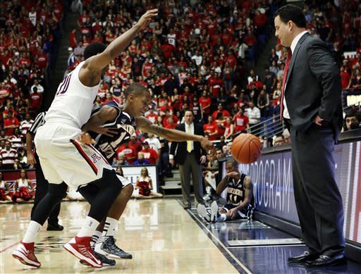 Northern Arizona's Dewayne Russell (12) loses the ball under pressure from Arizona's Jordin Mayes (20) and in front of Arizona head coach Sean Miller during the first half of an NCAA college basketball game at McKale Center in Tucson, Ariz., Wednesday, Nov. 28, 2012. (AP Photo/Wily Low)