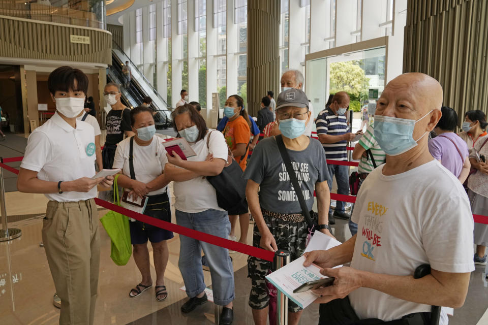 In this Tuesday, June 15, 2021 photo, people wearing face masks to help prevent the spread of the coronavirus, line up to register for a coronavirus vaccine lottery in a Grand Central residential building complex in Hong Kong. Coronavirus vaccine incentives offered by Hong Kong companies, including a lucky draw for an apartment, a Tesla car and even gold bars, are helping boost the city's sluggish inoculation rate. (AP Photo/Kin Cheung)