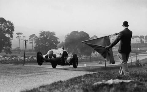 A Mercedes W 125 racing car in dramatic action at the Donington Park Grand Prix. The race was won by German racing driver Berndt Rosemeyer in an Auto Union. (Photo by Fox Photos/Getty Images) - Credit: Fox Photos/Hulton Archive