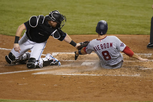Washington Nationals' Carter Kieboom (8) is tagged out, trying to steal home, by Miami Marlins catcher Chad Wallach during the fourth inning of a baseball game Saturday, Sept. 19, 2020, in Miami. (AP Photo/Lynne Sladky)