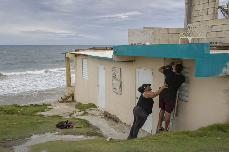 Ya Mary Morales, left, and Henry Sustache put plywood over the windows of their home as they prepare for the arrival of Tropical Storm Dorian on Aug. 28, 2019, in Yabucoa, Puerto Rico.