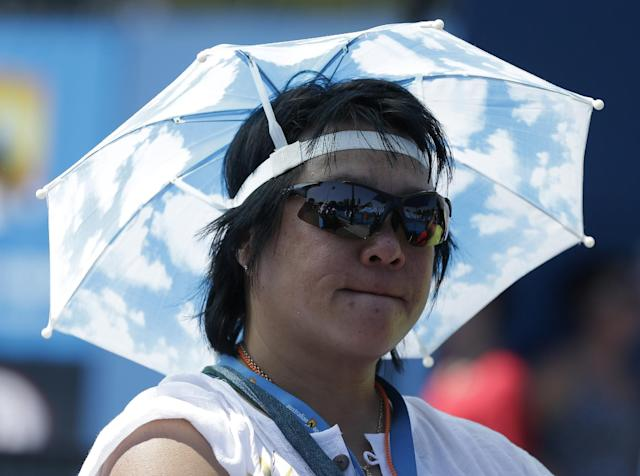 A spectator watches second round matches at the Australian Open tennis championship as temperatures are expected to top 44 C (112 F) in Melbourne, Australia, Thursday, Jan. 16, 2014. (AP Photo/Mark Baker)