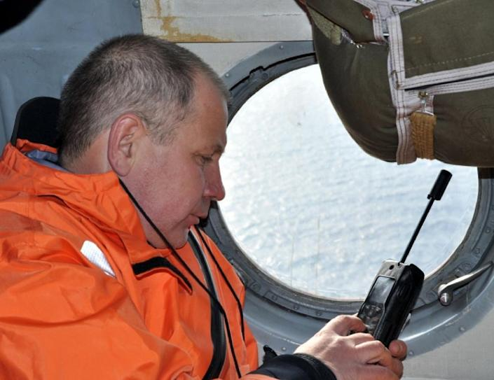 A rescuer using a satelite phone while onboard a helicopter in flight over the Sea of Okhotsk where the trawler Dalny Vostok has sunk on April 2, 2015 (AFP Photo/HO)