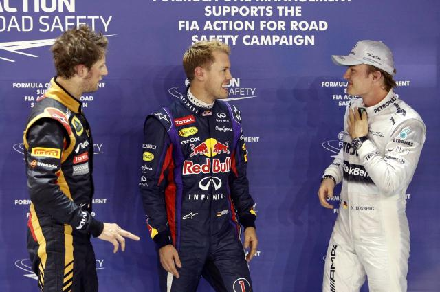 Lotus F1 Formula One driver Romain Grosjean of France (L), Red Bull Formula One driver Sebastian Vettel of Germany (C) and Mercedes Formula One driver Nico Rosberg of Germany (R) stand together after the qualifying session of the Singapore F1 Grand Prix at the Marina Bay street circuit in Singapore September 21, 2013. REUTERS/Tim Chong (SINGAPORE - Tags: SPORT MOTORSPORT F1)