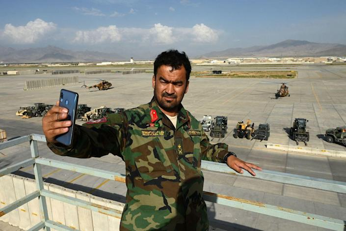 An Afghan soldier takes a selfie at the Bagram base
