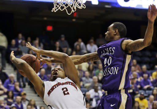 James Madison guard Devon Moore (40) blocks the shot of Northeastern guard Demetrius Pollard (2) during the first half of the Colonial Athletic Association Conference tournament championship NCAA college basketball game in Richmond, Va., Monday, March 11, 2013. (AP Photo/Steve Helber)