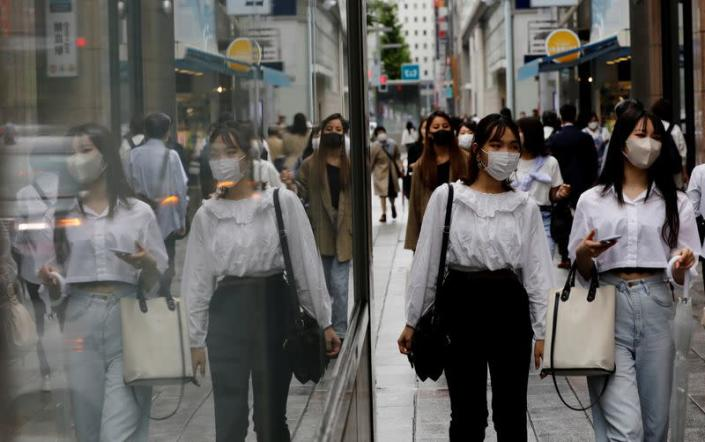 FILE PHOTO: People wearing protective masks in a shopping district in Tokyo,