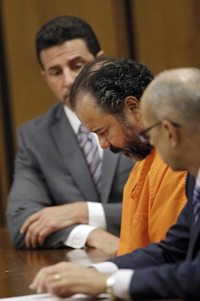 Ariel Castro, center, keeps his head bowed during a pretrial hearing in Cuyahoga County Common Pleas Court in Cleveland, Wednesday, July 3, 2013. Castro is accused of holding three women captive for nearly a decade. (AP Photo/Mark Duncan)
