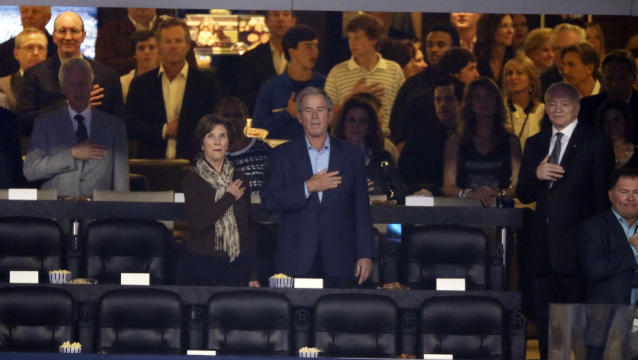 Former president George W. Bush and wife Laura stand during the national anthem with Dallas Cowboys owner Jerry Jones, right, before the NCAA Final Four tournament college basketball championship game between Connecticut and Kentucky, Monday, April 7, 2014, in Arlington, Texas. (AP Photo/Tony Gutierrez)