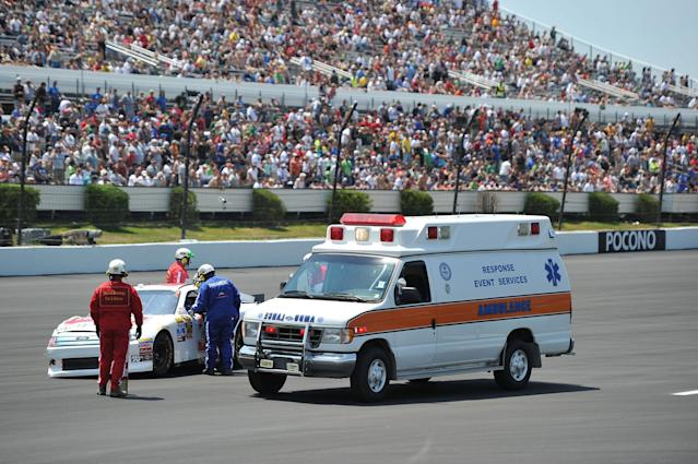 LONG POND, PA - JUNE 10: Safety crews tend to the #32 Herr Foods/Hero Energy shot Ford driven by Reed Sorenson after being involved in an on track incident in the NASCAR Sprint Cup Series Pocono 400 presented by #NASCAR at Pocono Raceway on June 10, 2012 in Long Pond, Pennsylvania. (Photo by Drew Hallowell/Getty Images)