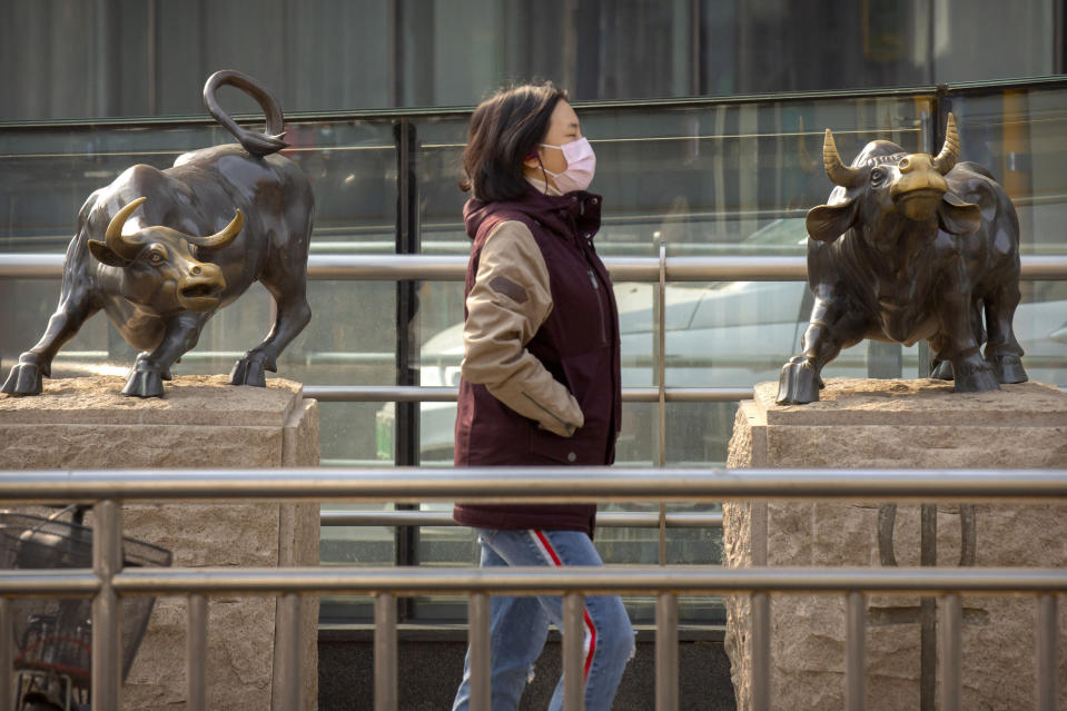 A woman wearing a face mask walks past statues of bulls in Beijing, Friday, Feb. 28, 2020. Asian stock markets fell further Friday on spreading virus fears, deepening an global rout after Wall Street endured its biggest one-day drop in nine years. (AP Photo/Mark Schiefelbein)