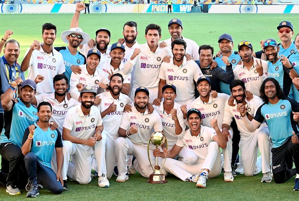 Indian players pose with the winning trophy after defeating Australia by three wickets on the final day of the fourth cricket test match at the Gabba, Brisbane, Australia, on Tuesday, 19 January 2021. India won the four test series 2-1.