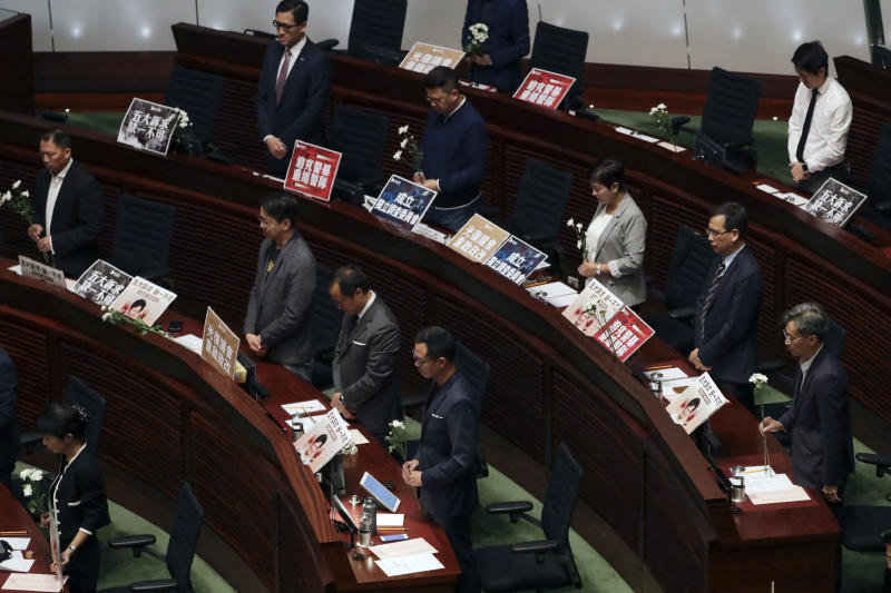 Pro-democracy lawmakers, some holding flowers, perform a silent prayer with protest plate card during a question and answer session with Hong Kong Chief Executive Carrie Lam at the chamber of the Legislative Council in Hong Kong, Thursday, Oct. 17, 2019. (AP Photo/Mark Schiefelbein)