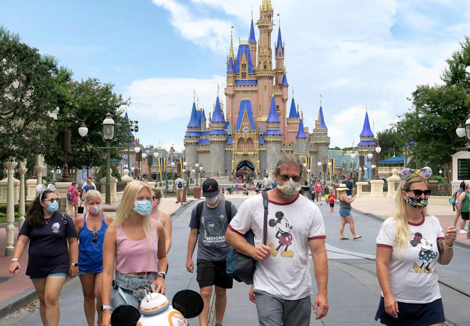 Guests wear masks as required to attend the official reopening day of the Magic Kingdom at Walt Disney World in Lake Buena Vista, Fla., Saturday, July 11, 2020. Disney reopened two Florida parks, the Magic Kingdom and Animal Kingdom, Saturday, with limited capacity and safety protocols in place in response to the coronavirus pandemic.