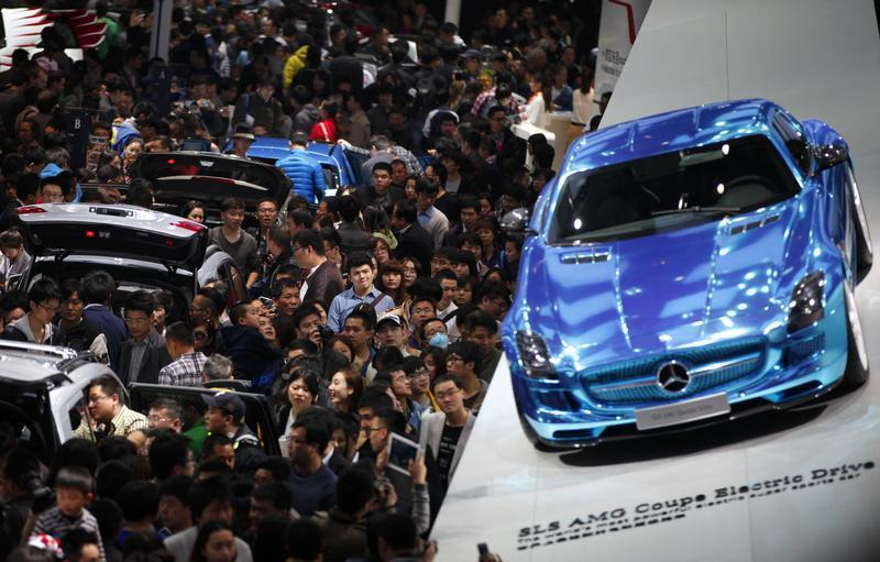 People looks at Mercedes-Benz cars during the the 15th Shanghai International Automobile Industry Exhibition in Shanghai