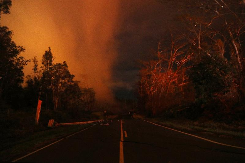 Lava illuminates volcanic gases (L) from the Kilauea volcano near fissure 13 on Hawaii's Big Island on May 16 -- the summit of the volcano erupted on Thursday (AFP Photo/MARIO TAMA)