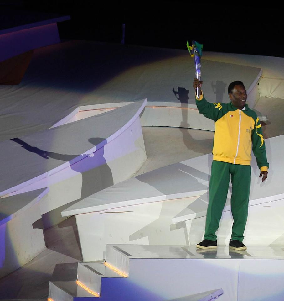 "Edson Arantes do Nacimento ""Pele"" holds the torch during the opening ceremony of the V World Military Games in Rio de Janeiro, Brazil on July 16, 2011. AFP PHOTO/JORGE PEREZ (Photo credit should read JORGE PEREZ/AFP/Getty Images)"
