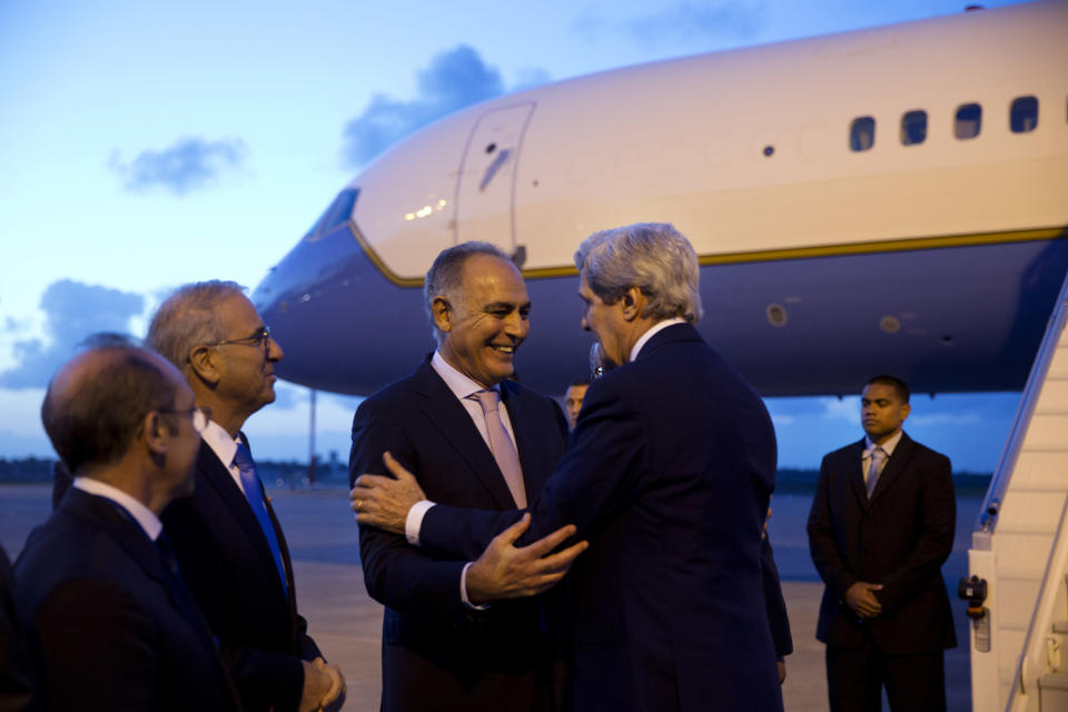 In this April 3, 2014, photo, U.S. Secretary of State John Kerry, right, is greeted by Moroccan Foreign Minister Salaheddine Mezouar on the secretary's arrival in Rabat, Morocco. The current trip was to have been a five-day trip to Europe and Saudi Arabia, but with crisis on multiple fronts and Kerry's decision on how to proceed turned a routine trip abroad into a frenetic tour of high-stakes diplomacy marked by abrupt changes in plan that have come to define his 14-month tenure as secretary of state. (AP Photo/Jacquelyn Martin, Pool)