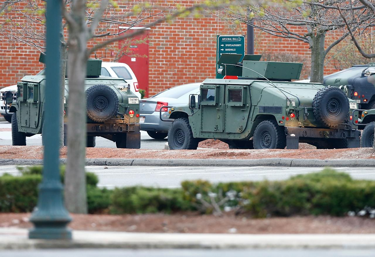 WATERTOWN, MA - APRIL 19: Military Police arrive in armoured vehicles at the parking lot of the Arsenal Mall on April 19, 2013 in Watertown, Massachusetts. Earlier, a Massachusetts Institute of Technology campus police officer was shot and killed late Thursday night at the school's campus in Cambridge. A short time later, police reported exchanging gunfire with alleged carjackers in Watertown, a city near Cambridge. According to reports, one suspect has been killed during a car chase and the police are seeking another - believed to be the same person (known as Suspect Two) wanted in connection with the deadly bombing at the Boston Marathon earlier this week. Police have confirmed that the dead assailant is Suspect One from the recently released marathon bombing photographs.  (Photo by Jared Wickerham/Getty Images)