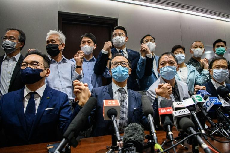 Pro-democracy lawmakers join hands during a press conference in Hong Kong on November 11, 2020 when they said they would all resign, after China gave the city the power to disqualify politicians deemed a threat to national security