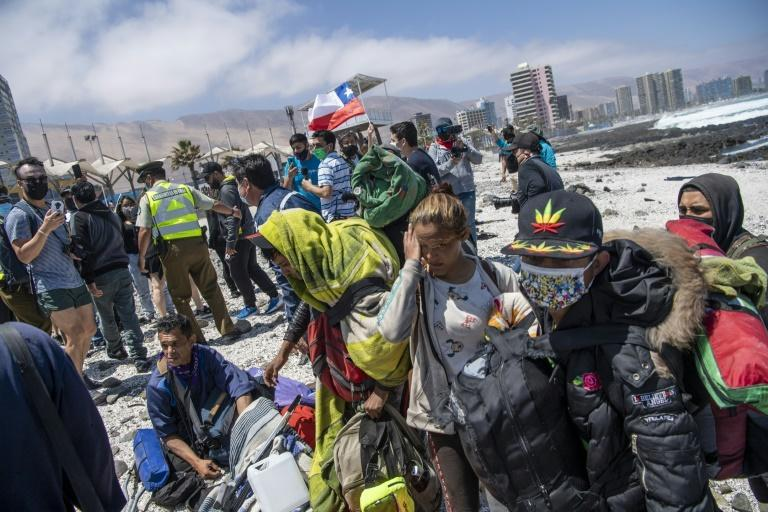 Venezuelan migrants take refuge on the seashore to avoid being attacked by demonstrators during a march in Iquique, Chile on September 25, 2021 (AFP/MARTIN BERNETTI)